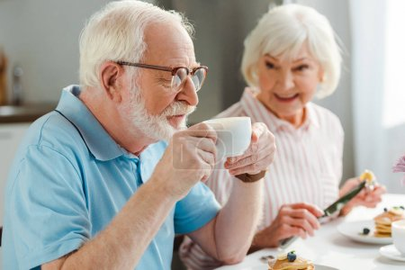 Photo for Selective focus of senior man drinking coffee by smiling wife with pancakes during breakfast - Royalty Free Image