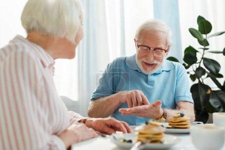 Photo pour Concentration sélective de l'homme âgé parlant à sa femme par le café et les crêpes sur la table - image libre de droit