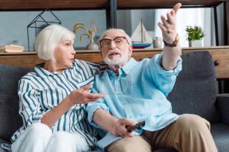 Photo pour Focus sélectif de l'homme âgé en train de gesticuler en regardant la télévision avec sa femme sur le divan dans le salon - image libre de droit