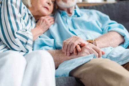 Photo for Selective focus of elderly couple holding hands while sitting on couch - Royalty Free Image