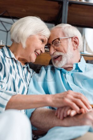 Photo for Selective focus of senior couple smiling at each other while holding hands on sofa - Royalty Free Image