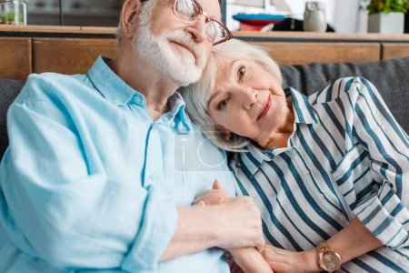 Photo for Senior woman looking at camera while holding hand of husband on sofa - Royalty Free Image
