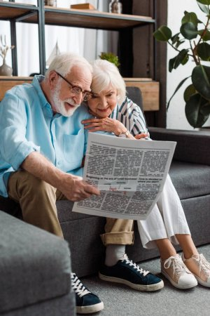 Photo for Smiling senior woman sitting by husband with newspaper on couch at home - Royalty Free Image