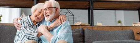 Photo pour Plan panoramique d'une femme âgée souriante embrassant son mari sur un canapé à la maison - image libre de droit