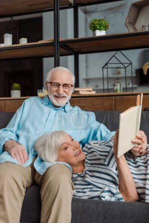 Photo for Senior woman reading book by smiling husband on couch at home - Royalty Free Image