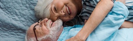 Photo for Top view of smiling senior couple hugging on bed, panoramic shot - Royalty Free Image