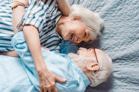 Photo pour Vue en haut d'un couple de personnes âgées se souriant au lit - image libre de droit