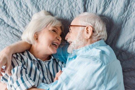 Photo pour Vue du haut d'un couple d'aînés souriant allongé sur le lit - image libre de droit