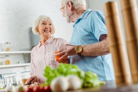 Photo pour Choix de la femme souriante qui regarde son mari en train de cuisiner sur une table de cuisine - image libre de droit