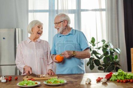 Photo pour Focus sélective de la femme âgée rire en coupant des légumes par mari dans la cuisine - image libre de droit