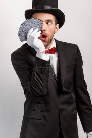 Photo pour Magicien choqué avec bouche ouverte tenant des cartes à jouer, isolé sur gris - image libre de droit