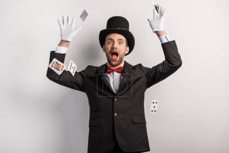 Photo pour Magicien surpris jetant des cartes à jouer, sur gris - image libre de droit