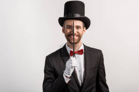 Photo pour Gai magicien en costume et chapeau tenant baguette, isolé sur gris - image libre de droit