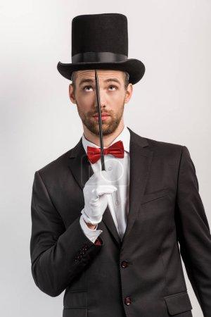 Photo pour Magicien réfléchi en costume et chapeau tenant baguette, isolé sur gris - image libre de droit
