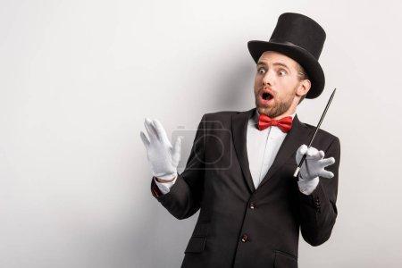 Photo pour Magicien choqué avec baguette magique à bouche ouverte, isolé sur gris - image libre de droit