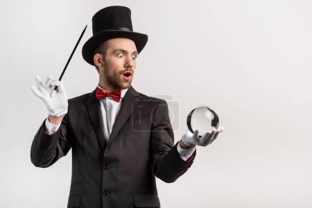 Photo pour Magicien choqué tenant baguette magique et balle magique, isolé sur gris - image libre de droit