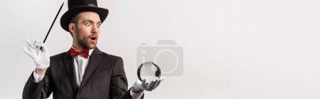 Photo pour Plan panoramique de magicien choqué tenant baguette magique et balle magique, isolé sur gris - image libre de droit