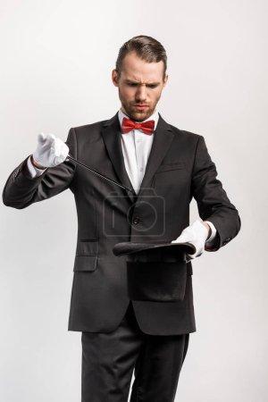 Photo pour Magicien confus en costume faisant tour chapeau et baguette, isolé sur gris - image libre de droit