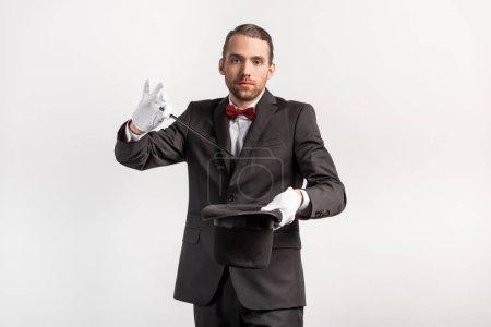 Photo pour Magicien en costume faisant tour chapeau et baguette, isolé sur gris - image libre de droit