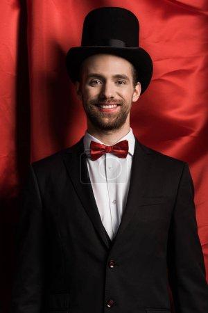 Photo pour Beau magicien souriant en costume et chapeau dans le cirque avec des rideaux rouges - image libre de droit