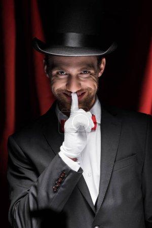 Photo pour Magicien souriant montrant symbole de silence dans le cirque avec des rideaux rouges - image libre de droit