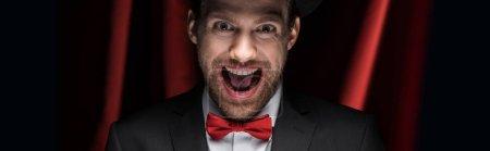 Photo pour Plan panoramique de magicien excité effrayant avec bouche ouverte dans un cirque avec des rideaux rouges - image libre de droit