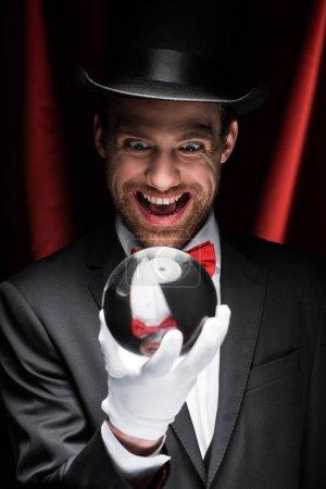 Photo pour Excité effrayant magicien regardant boule magique dans le cirque avec des rideaux rouges - image libre de droit