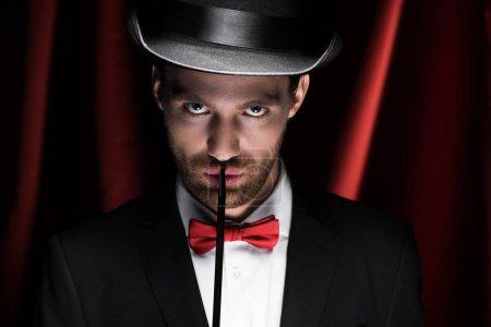 Photo pour Magicien confiant en costume et chapeau tenant baguette dans le cirque avec rideaux rouges - image libre de droit