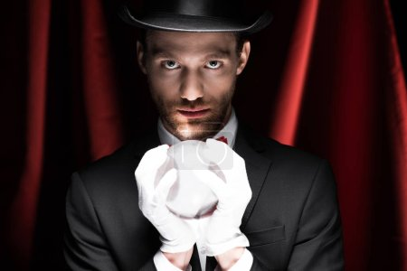 Photo pour Magicien professionnel tenant boule magique dans le cirque avec des rideaux rouges - image libre de droit