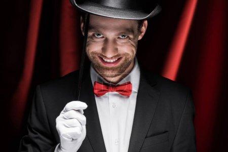 Photo pour Magicien effrayant souriant en costume et chapeau tenant baguette dans le cirque avec rideaux rouges - image libre de droit