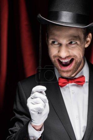 Photo pour Magicien excité à bouche ouverte tenant baguette dans le cirque avec rideaux rouges - image libre de droit