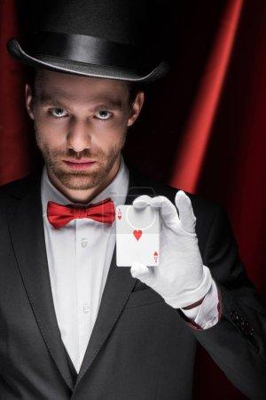 Photo pour Magicien professionnel tenant des cartes à jouer dans un cirque avec des rideaux rouges - image libre de droit