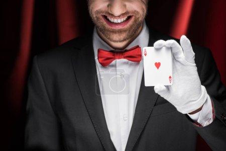 Photo pour Vue recadrée d'un magicien souriant tenant des cartes à jouer dans un cirque avec des rideaux rouges - image libre de droit