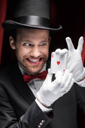 Photo pour Effrayant sourire magicien tenant des cartes à jouer dans le cirque avec des rideaux rouges - image libre de droit