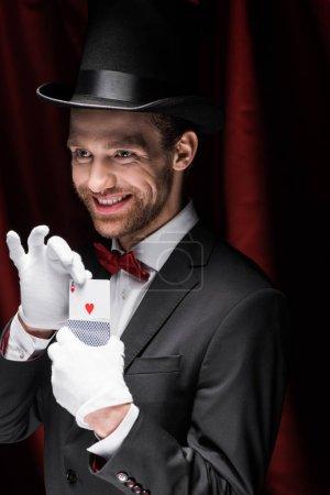 Photo pour Magicien souriant tenant des cartes à jouer dans un cirque avec des rideaux rouges - image libre de droit
