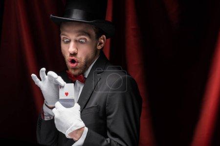 Photo pour Magicien choqué tenant des cartes à jouer dans le cirque avec des rideaux rouges - image libre de droit