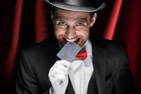 Photo pour Magicien souriant tenant la carte à jouer dans les dents dans le cirque avec des rideaux rouges - image libre de droit