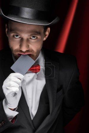 Photo pour Magicien professionnel montrant tour avec carte à jouer dans le cirque avec des rideaux rouges - image libre de droit