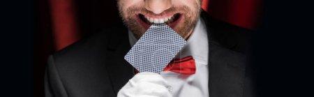 Photo pour Vue recadrée du magicien souriant tenant la carte à jouer dans les dents dans le cirque avec des rideaux rouges, vue panoramique - image libre de droit