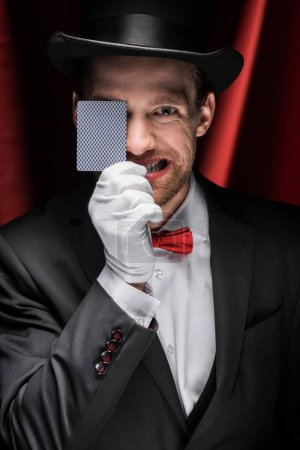 Photo pour Magicien émotionnel montrant tour avec carte à jouer dans le cirque avec des rideaux rouges - image libre de droit