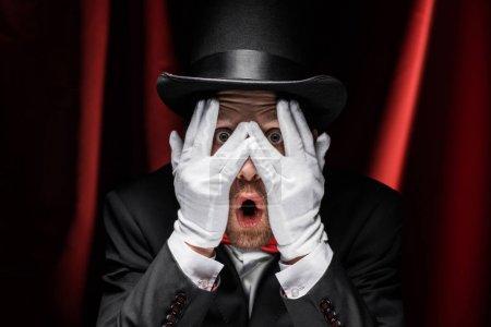 Photo pour Magicien choqué fermer les yeux avec les mains dans des gants dans le cirque avec des rideaux rouges - image libre de droit