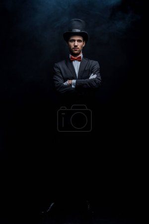 Photo for Magician in suit and hat standing with crossed arms in dark smoky room - Royalty Free Image