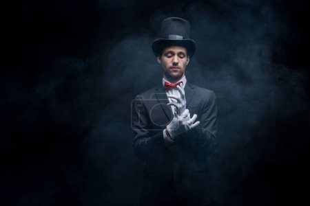 Photo for Magician in suit and hat wearing gloves in dark smoky room - Royalty Free Image