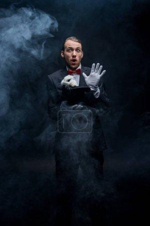 Photo pour Magicien émotionnel en costume tenant chapeau avec lapin blanc, chambre sombre avec fumée - image libre de droit