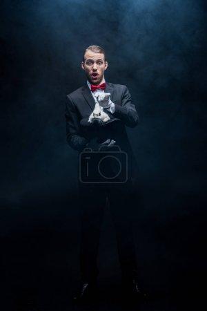 Photo pour Magicien excité en costume montrant un truc avec lapin blanc en chapeau, chambre noire avec fumée - image libre de droit