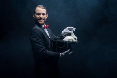 Photo pour Magicien joyeux en costume montrant tour avec lapin blanc dans le chapeau, chambre sombre avec de la fumée - image libre de droit