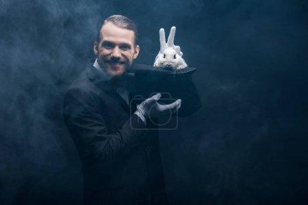 Photo pour Magicien positif en costume montrant tour avec lapin blanc dans le chapeau, chambre sombre avec de la fumée - image libre de droit