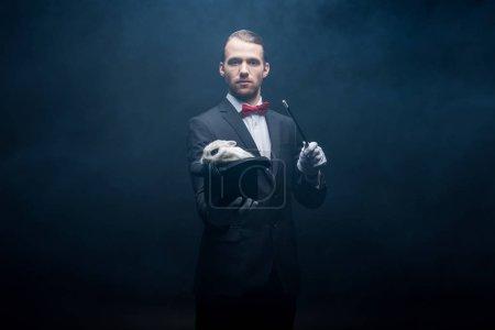 Photo pour Magicien professionnel sérieux en costume montrant tour avec baguette et lapin blanc dans le chapeau, chambre sombre avec fumée - image libre de droit