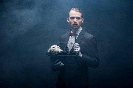 Photo pour Magicien en costume montrant tour avec baguette et lapin blanc dans le chapeau, chambre sombre avec fumée - image libre de droit