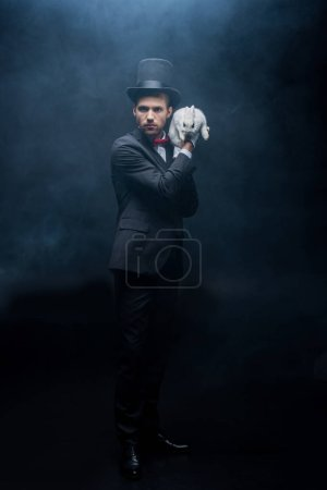 Photo for Serious magician in suit and hat holding white rabbit, dark room with smoke - Royalty Free Image